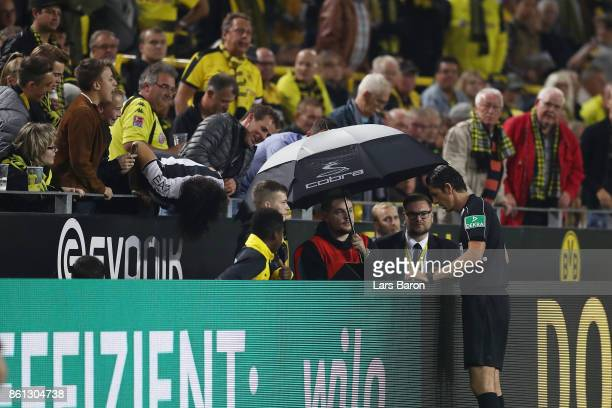 Referee Deniz Aytekin looks at the video footage to clarify a situation that eventually leads to a penalty for Dortmund during the Bundesliga match...