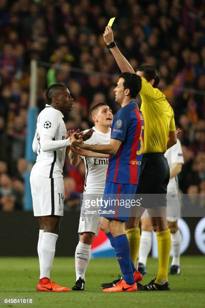 Referee Deniz Aytekin of Germany gives a yellow card to Blaise Matuidi of PSG while Marco Verratti looks on during the UEFA Champions League Round of...