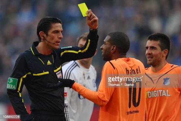 Referee Deniz Aytekin shows the yellow card to Ryan Babel of Hoffenheim during the Bundesliga match between FC Schalke 04 and 1899 Hoffenheim at...