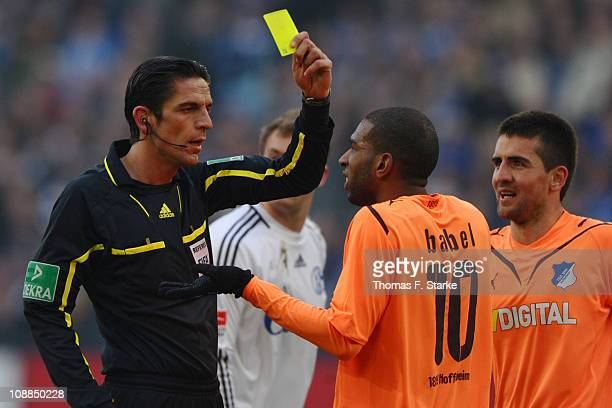 Referee Deniz Aytekin shows the yellow card to Ryan Babel of Hoffenheim during the Bundesliga match between FC Schalke 04 and 1899 Hoffenheim at...