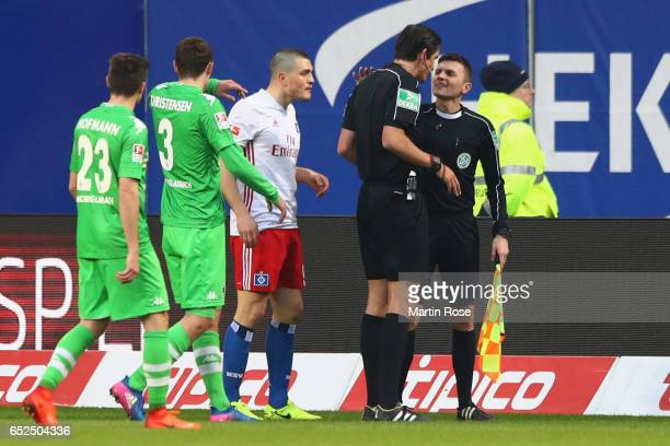 Referee Deniz Aytekin talks to assistent referee Eduard Beitlinger during the Bundesliga match between Hamburger SV and Borussia Moenchengladbach at...