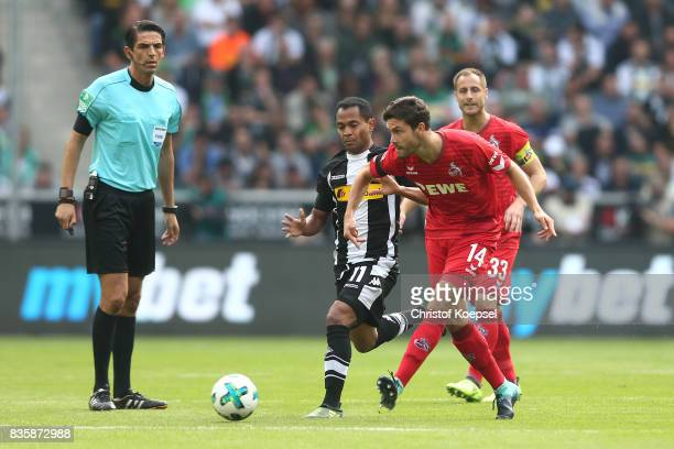 Referee Deniz Aytekin watches Raffael of Moenchengladbach Jonas Hector of Koeln and Matthias Lehmann of Koeln during the Bundesliga match between...