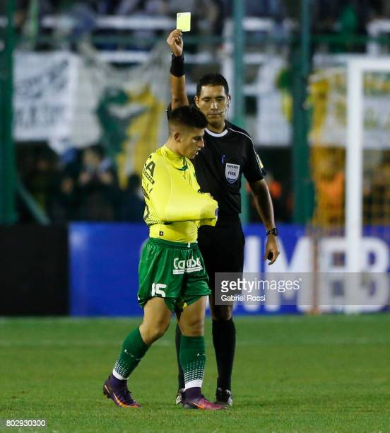 Referee Diego Haro shows a yellow card to Nicolas Stefanelli of Defensa y Justicia during a first leg match between Defensa y Justicia and...