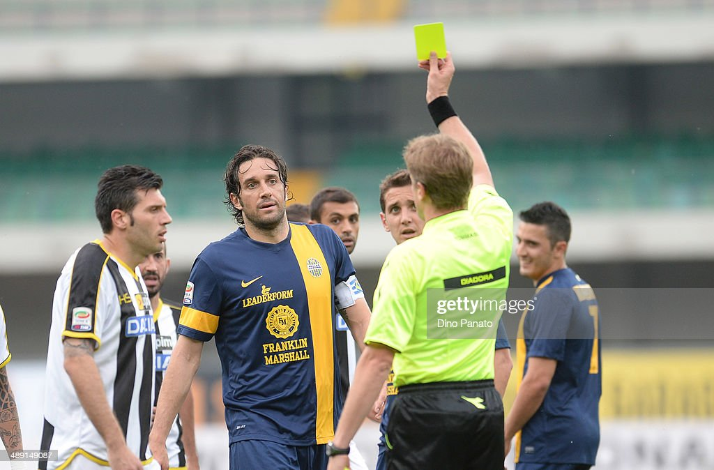 Referee Dino Tommasi (R) shows yellow card to Martinho Alves De Lima of Hellas Verona and Maurizio Domizzi (L) of Udinese Calcio during the Serie A match between Hellas Verona FC and Udinese Calcio at Stadio Marc'Antonio Bentegodi on May 10, 2014 in Verona, Italy.