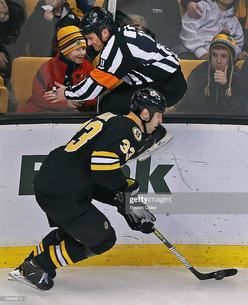 A referee (#11) does a good job of getting out of the way of the Bruins' Zdeno Chara by quickly jumping up in the air to avoid the Boston captain in the third period as the Boston Bruins hosted the Winnipeg Jets in an NHL regular season game at the TD Garden.
