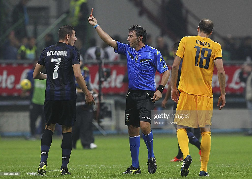 Referee Domenico Celi (C) shows the red card to <a gi-track='captionPersonalityLinkClicked' href=/galleries/search?phrase=Ishak+Belfodil&family=editorial&specificpeople=6175690 ng-click='$event.stopPropagation()'>Ishak Belfodil</a> (L) of FC Internazionale Milano at the end of the Serie A match between FC Internazionale Milano and Hellas Verona at Stadio Giuseppe Meazza on October 26, 2013 in Milan, Italy.