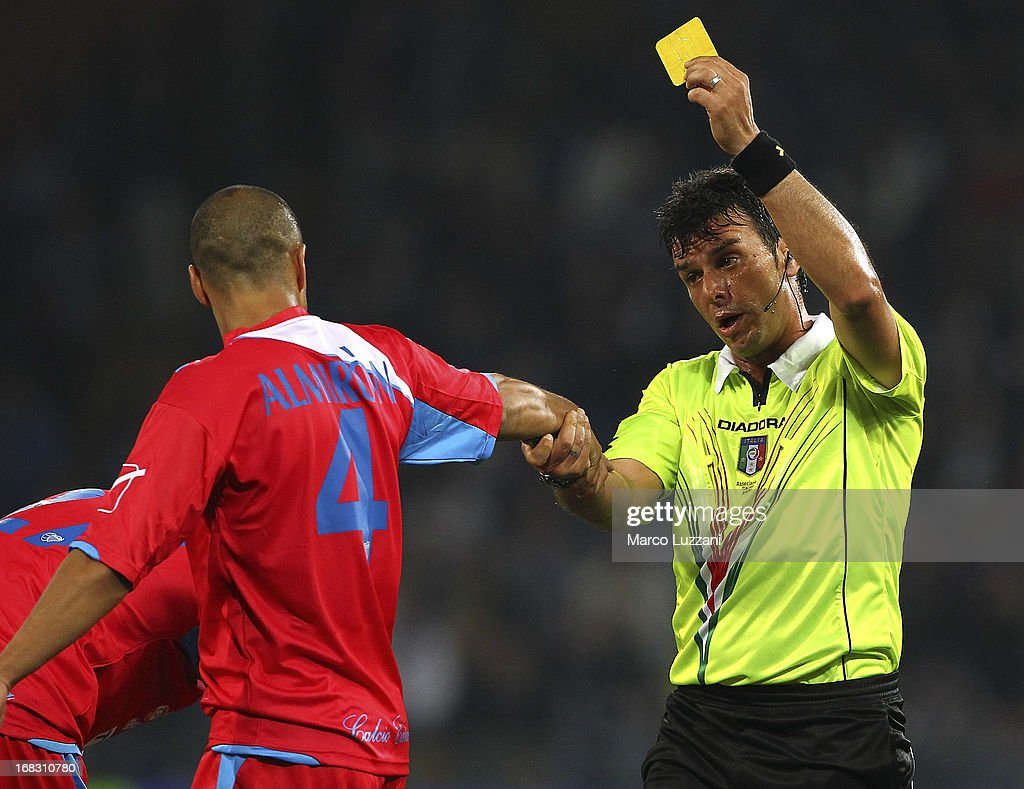 Referee Domenico Celi shows the yellow card to Sergio Bernardo Almiron of Calcio Catania during the Serie A match between UC Sampdoria and Calcio Catania at Stadio Luigi Ferraris on May 8, 2013 in Genoa, Italy.