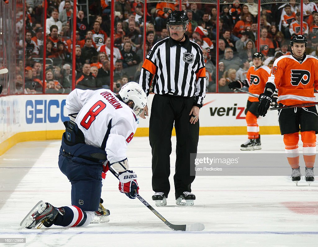 Referee Don VanMassenhoven #21 watches Alex Ovechkin #8 of the Washington Capitals react after being high-sticked by Braydon Coburn #5 (not pictured) of the Philadelphia Flyers on February 27, 2013 at the Wells Fargo Center in Philadelphia, Pennsylvania.