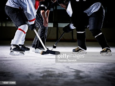 Referee dropping hockey puck for faceoff