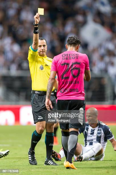 Referee Eduardo Galvan gives a yellow card to Robert Herrera of Pachuca during the 13th round match between Monterrey and Pachuca as part of the...