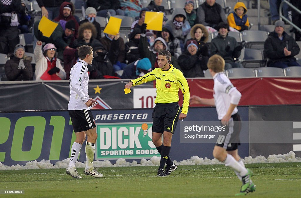 Referee Elias Bazakos gives a yellow card to Marc Burch of DC United for a foul against the Colorado Rapids as the fans present yellow cards of their...