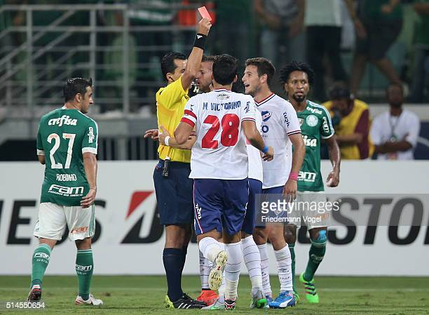Referee Enrique Osses gives Vitor Hugo of Nacional the red card during a match between Palmeiras and Nacional as part of Group 2 of Copa Bridgestone...
