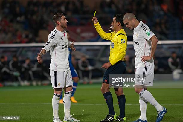 Referee Enrique Roberto Osses Zencovich shows Sergio Ramos of Real Madrid a yellow card during the 2014 FIFA Club World Cup semi final soccer match...