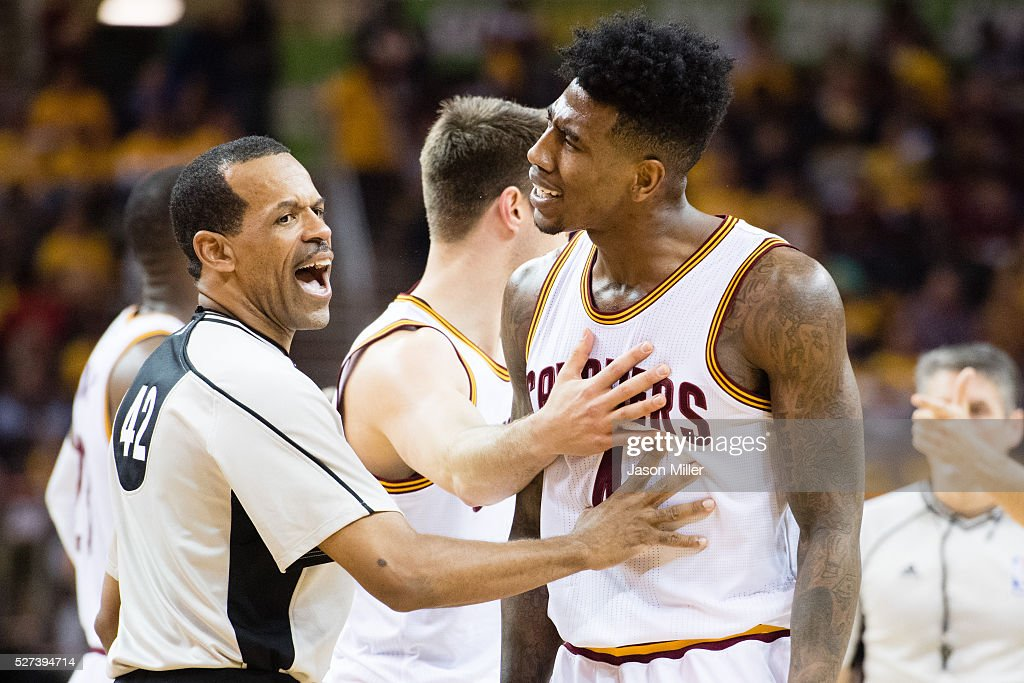 Referee Eric Lewis tries to stop Iman Shumpert of the Cleveland Cavaliers from arguing with a member of the Atlanta Hawks team during the second half...