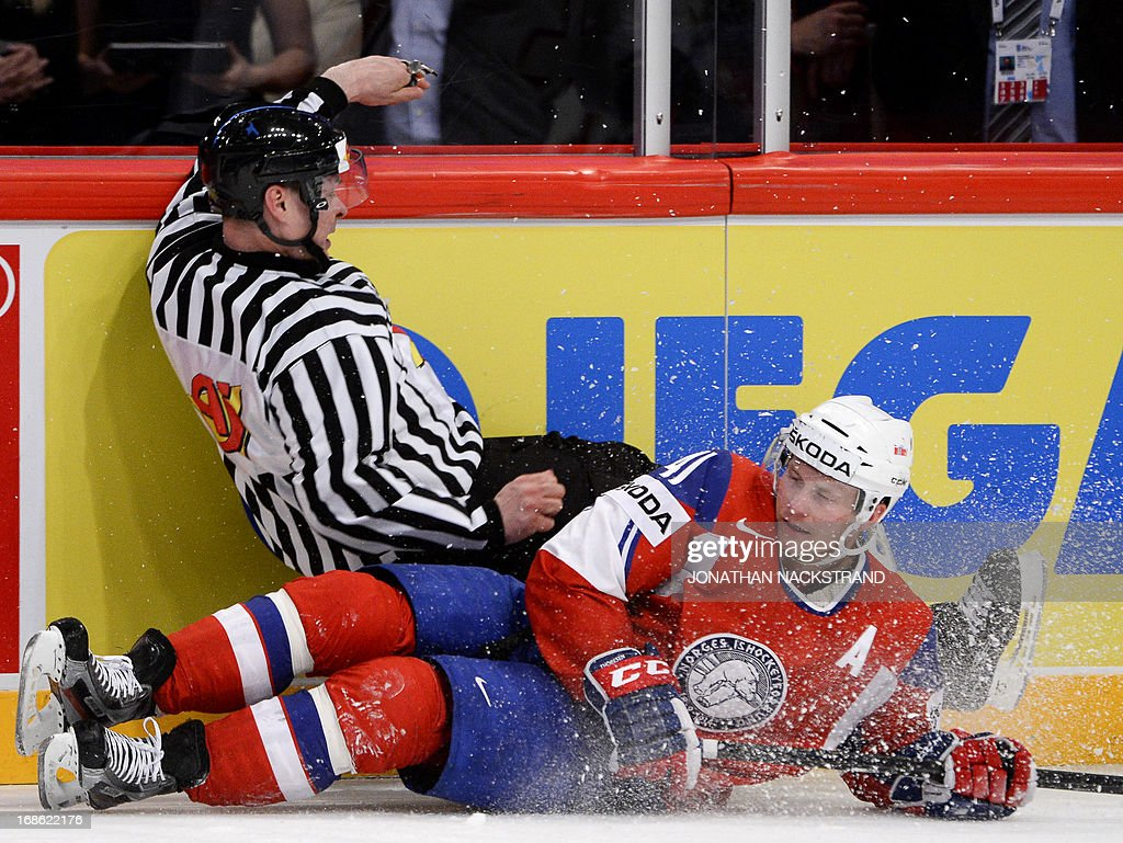 A referee falls on Norway's Patrick Thoresen during the preliminary round match Norway vs Switzerland at the 2013 IIHF Ice Hockey World Championships on May 12, 2013 in Stockholm. Switzerland won 3-1.
