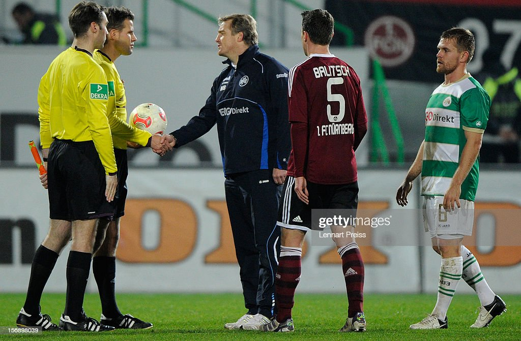 Referee <a gi-track='captionPersonalityLinkClicked' href=/galleries/search?phrase=Felix+Brych&family=editorial&specificpeople=707645 ng-click='$event.stopPropagation()'>Felix Brych</a> (2nd L) and Michael Bueskens (C), head coach of Fuerth, shake hands after the Bundesliga match between SpVgg Greuther Fuerth and 1. FC Nuernberg at Trolli-Arena on November 24, 2012 in Fuerth, Germany.