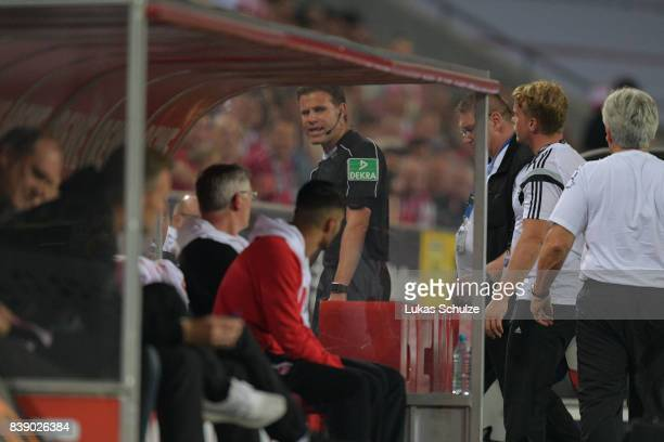 Referee Felix Brych leaves has to leave the match with an injury during the Bundesliga match between 1 FC Koeln and Hamburger SV at...
