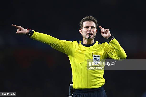 Referee Felix Brych points during the UEFA Champions League Group A match between Arsenal FC and Paris SaintGermain at the Emirates Stadium on...
