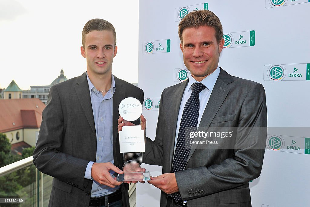 Referee <a gi-track='captionPersonalityLinkClicked' href=/galleries/search?phrase=Felix+Brych&family=editorial&specificpeople=707645 ng-click='$event.stopPropagation()'>Felix Brych</a> (R) receives the trophy for the Referee Of The Year 2013 award of his colleague Michael Bacher during the Referee Of The Year 2013 awarding ceremony at Hotel Bayerischer Hof on August 29, 2013 in Munich, Germany.