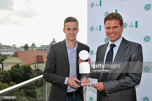 Referee Felix Brych receives the trophy for the Referee Of The Year 2013 award of his colleague Michael Bacher during the Referee Of The Year 2013...