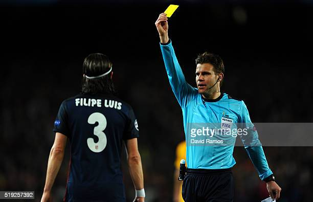 Referee Felix Brych shows a yellow card to Felipe Luis of Atletico Madrid during the UEFA Champions League quarter final first leg match between FC...