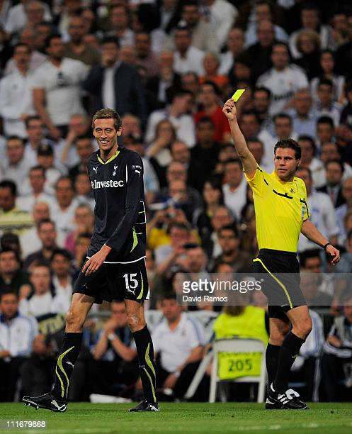 Referee Felix Brych shows a yellow card to Peter Crouch of Tottenham Hotspur during the UEFA Champions League quarter final first leg match between...