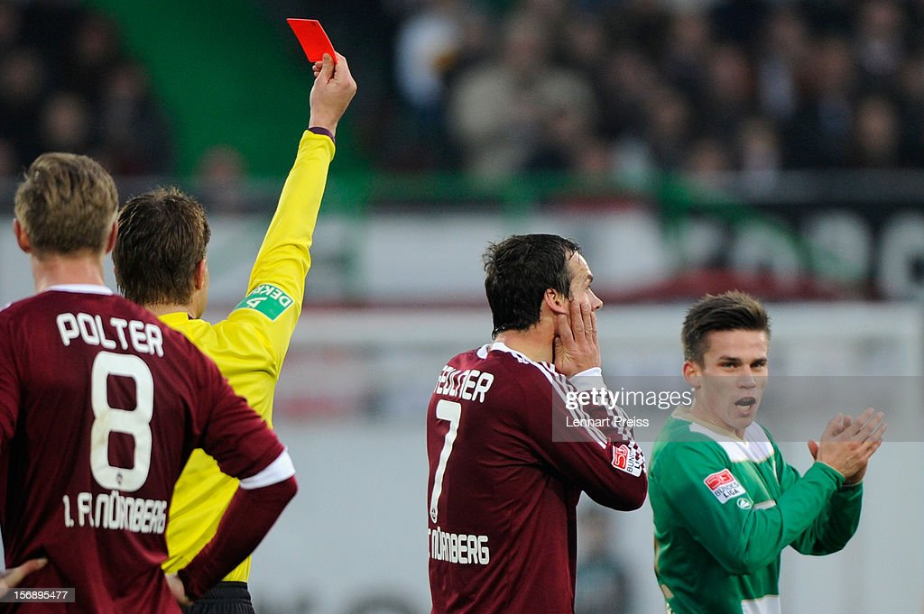 Referee <a gi-track='captionPersonalityLinkClicked' href=/galleries/search?phrase=Felix+Brych&family=editorial&specificpeople=707645 ng-click='$event.stopPropagation()'>Felix Brych</a> (2nd L) shows <a gi-track='captionPersonalityLinkClicked' href=/galleries/search?phrase=Markus+Feulner&family=editorial&specificpeople=623655 ng-click='$event.stopPropagation()'>Markus Feulner</a> of Nuernberg the red card during the Bundesliga match between SpVgg Greuther Fuerth and 1. FC Nuernberg at Trolli-Arena on November 24, 2012 in Fuerth, Germany.