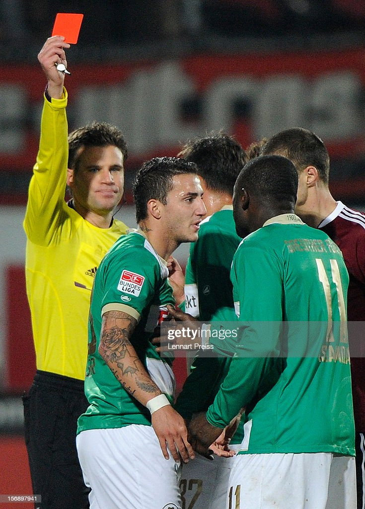 Referee <a gi-track='captionPersonalityLinkClicked' href=/galleries/search?phrase=Felix+Brych&family=editorial&specificpeople=707645 ng-click='$event.stopPropagation()'>Felix Brych</a> (L) shows Sercan Sararer (2nd L) of Fuerth the red card during the Bundesliga match between SpVgg Greuther Fuerth and 1. FC Nuernberg at Trolli-Arena on November 24, 2012 in Fuerth, Germany.