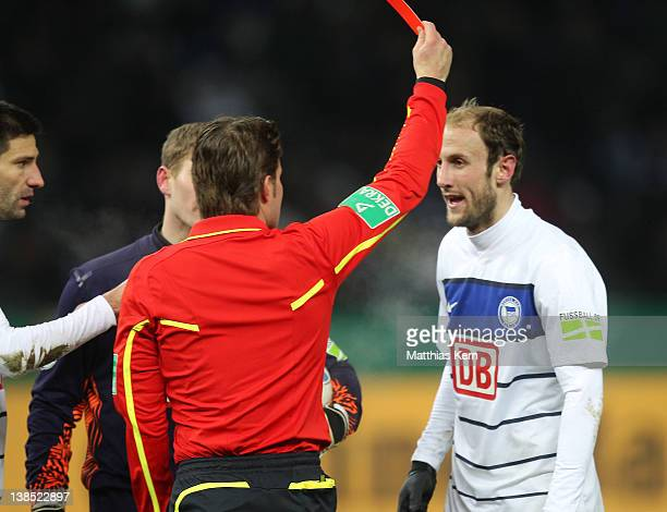 Referee Felix Brych shows the red card to Roman Hubnik of Berlin during the DFB Cup Quarter Final match between Hertha BSC Berlin and Borussia...