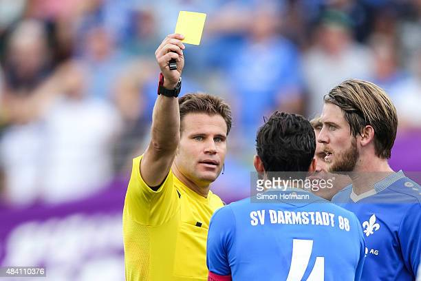 Referee Felix Brych shows the yellow card to Aytac Sulu during the Bundesliga match between SV Darmstadt 98 and Hannover 96 at MerckStadion am...