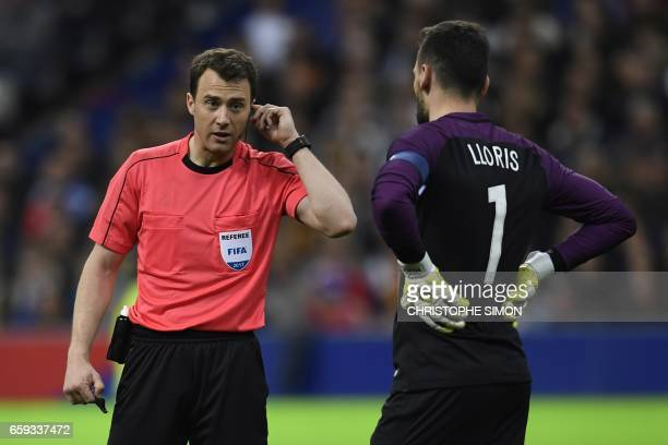 TOPSHOT Referee Felix Swayer asks video assitance next to Hugo Lloris France's goalkeeper during the friendly football match France vs Spain on March...