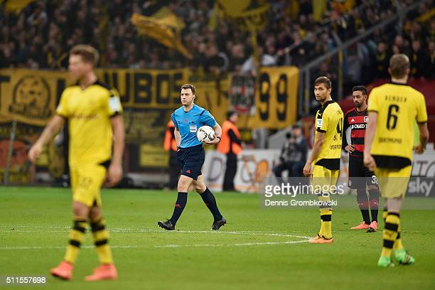 Referee Felix Zwayer returns to the pitch after he had suspended the match during the Bundesliga match between Bayer Leverkusen and Borussia Dortmund...