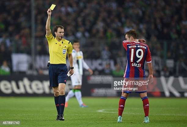 Referee Felix Zwayer shows a yellow card to Mario Goetze of Muenchen during the Bundesliga match between Borussia Moenchengladbach and FC Bayern...