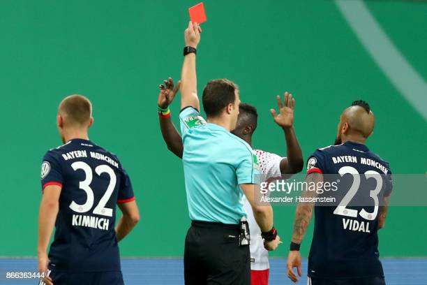 Referee Felix Zwayer shows Naby Deco Keita of Leipzig the Red card during the DFB Cup round 2 match between RB Leipzig and Bayern Muenchen at Red...