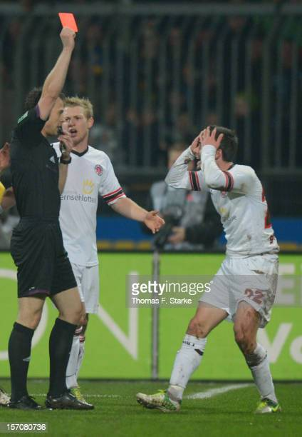 Referee Felix Zwayer shows the red card to Fin Bartels of St Pauli while Patrick Funk of St Pauli reacts during the Second Bundesliga match between...