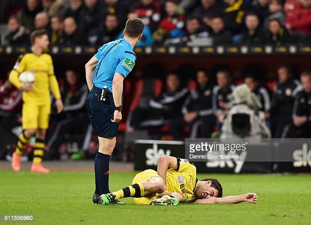 Referee Felix Zwayer stands over an injured Sokratis Papastathopoulos of Borussia Dortmund during the Bundesliga match between Bayer Leverkusen and...