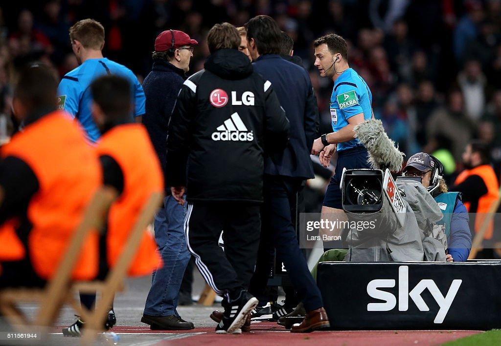 Referee Felix Zwayer walks past Roger Schmidt head coach of Bayer Leverkusen as he suspends the match after Borussia Dortmund's first goal during the Bundesliga match between Bayer Leverkusen and Borussia Dortmund at BayArena on February 21, 2016 in Leverkusen, Germany.