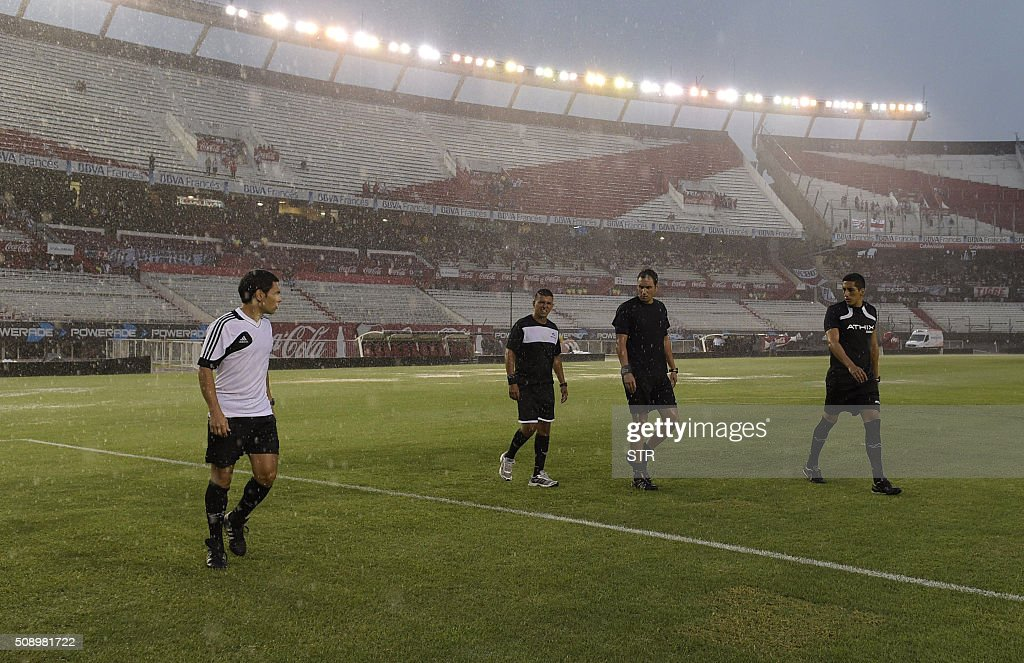 Referee Fernando Rapallini (2-R) and the assistant and fourth referees walk the pitch of the Monumental Stadium during a heavy rainstorm before the suspension of the Argentine first division football match between River Plate and Quilmes in Buenos Aires, Argentina, on February 7, 2016. AFP PHOTO / STR / AFP / STR