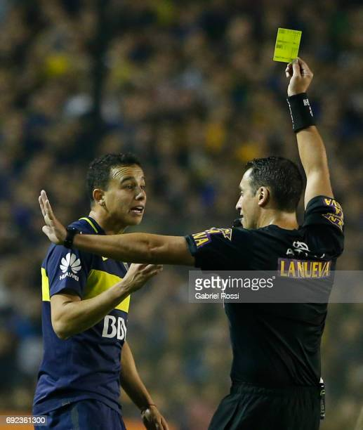 Referee Fernando Rapallini shows a yellow card to Leonardo Jara of Boca Juniors during a match between Boca Juniors and Independiente as part of...