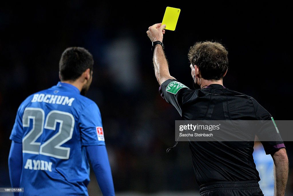 Referee <a gi-track='captionPersonalityLinkClicked' href=/galleries/search?phrase=Florian+Meyer&family=editorial&specificpeople=5788868 ng-click='$event.stopPropagation()'>Florian Meyer</a> (R) shows yellow card to Mirkan Aydin (L) of Bochum during the Second Bundesliga match between VfL Bochum and 1. FC Kaiserslautern at Rewirpower Stadion on October 28, 2013 in Bochum, Germany.