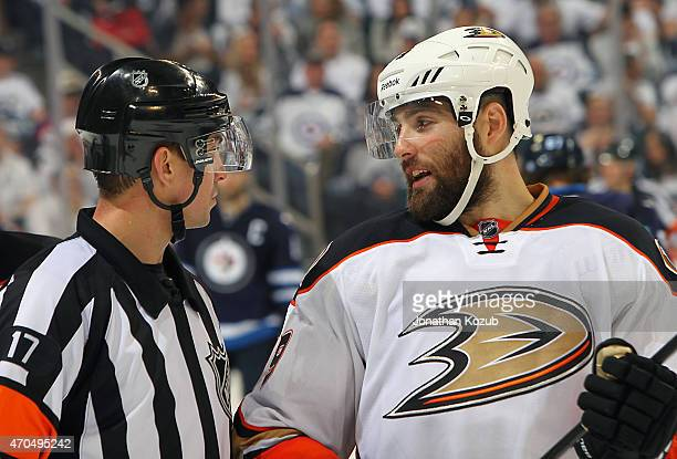 Referee Frederick L'Ecuyer chats with Patrick Maroon of the Anaheim Ducks during a third period stoppage in play against the Winnipeg Jets in Game...