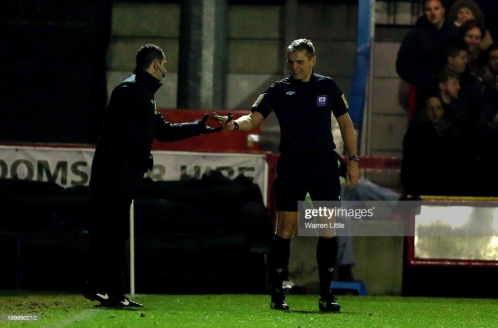 Referee G Scott removes a banana after being thrown on the pitch during the npower League Two match between AFC Wimbledon and Port Vale at The Cherry Red Records Stadium on January 24, 2013 in Kingston upon Thames, England.