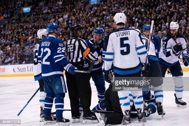 NHL referee Ghislain Hebert holds back Toronto Maple Leafs Defenceman Morgan Rielly during the third period of the NHL regular season game between...