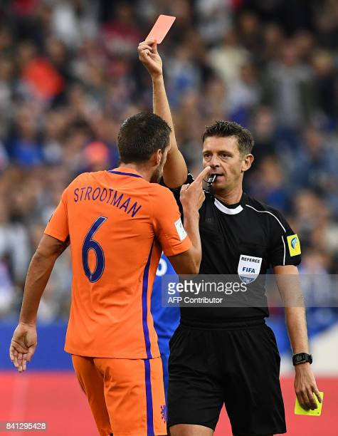 Referee Gianluca Rocchi gives a red card to Netherlands' midfielder Kevin Strootman during the 2018 FIFA World Cup qualifying football match France...