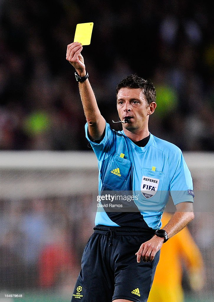 Referee Gianluca Rocchi shows a is shown a yellow card to Javier Mascherano of FC Barcelona during the UEFA Champions League Group G match between FC Barcelona and Celtic FC at the Camp Nou Stadium on October 23, 2012 in Barcelona, Spain. FC Barcelona won 2-1.