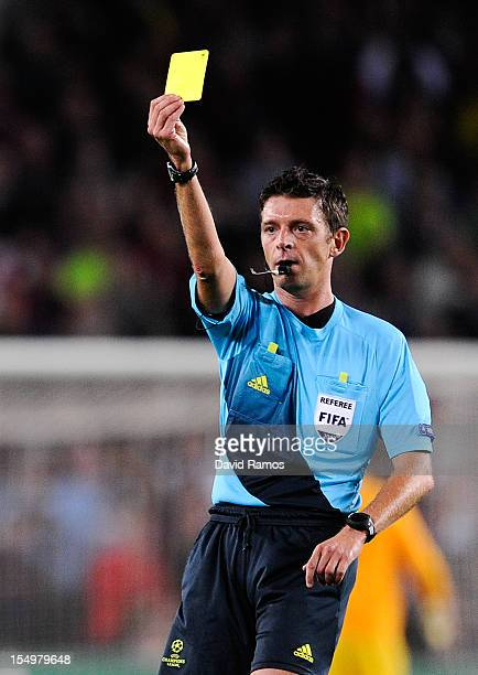 Referee Gianluca Rocchi shows a is shown a yellow card to Javier Mascherano of FC Barcelona during the UEFA Champions League Group G match between FC...