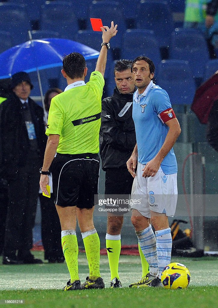 Referee Gianluca Rocchi shows a red card to <a gi-track='captionPersonalityLinkClicked' href=/galleries/search?phrase=Stefano+Mauri&family=editorial&specificpeople=676361 ng-click='$event.stopPropagation()'>Stefano Mauri</a> of SS Lazio during the Serie A match between S.S. Lazio and AS Roma at Stadio Olimpico on November 11, 2012 in Rome, Italy.
