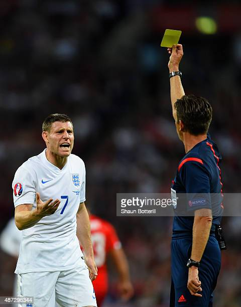 Referee Gianluca Rocchi shows James Milner of England a yellow card during the UEFA EURO 2016 Group E qualifying match between England and...