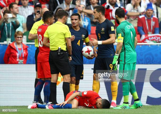 Referee Gianluca Rocchi speaks with Tim Cahill of Australia as Alexis Sanchez of Chile is down injured during the FIFA Confederations Cup Russia 2017...