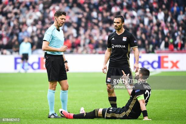 Referee Gianluca Rocchi talks with Jeremy Morel and Maxime Gonalons of Lyon during the Uefa Europa League semi final first leg match between Ajax...